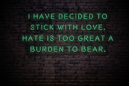 Neon sign with wise quote on brick wall in the darkness.