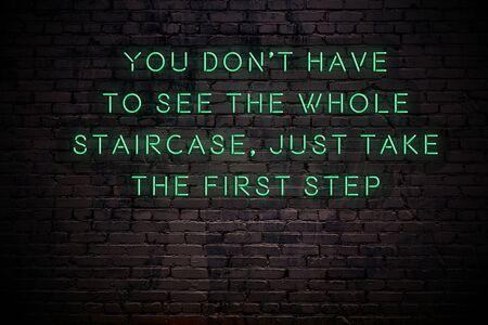Enseigne au néon avec citation sage sur mur de briques dans l'obscurité.