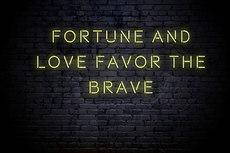 Neon inscription of sensible quote against brick wall at night.