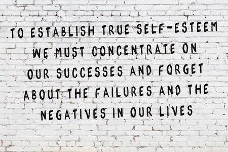 Painted black inscription on white brick wall. Фото со стока