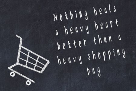 Chalk drawing of shopping cart and short quote about shopping on black board. Foto de archivo