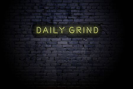 Highlighted brick wall with neon inscription daily grind.