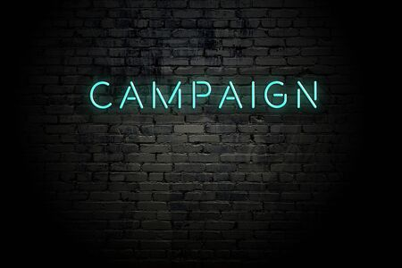 Highlighted brick wall with neon inscription campaign.