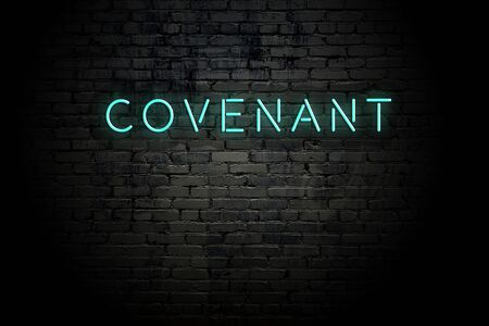 Highlighted brick wall with neon inscription covenant.