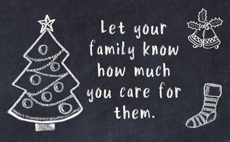 Drawing of christmas tree and handwritten greetings on black chalkboard . 版權商用圖片 - 131407517
