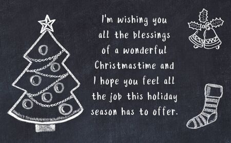 Drawing of christmas tree and handwritten greetings on black chalkboard .