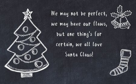 Drawing of christmas tree and handwritten greetings on black chalkboard . Stock Photo