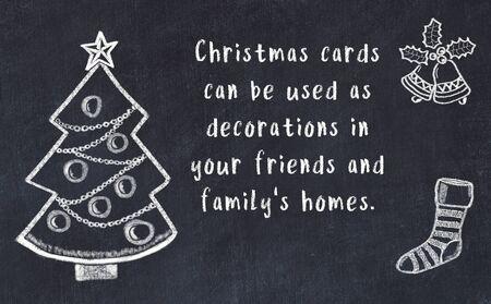 Drawing of christmas tree and handwritten greetings on black chalkboard . Standard-Bild