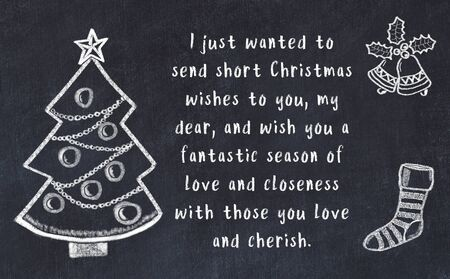 Drawing of christmas tree and handwritten greetings on black chalkboard .