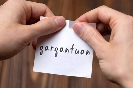 Dealing with problem concept. Hands tearing paper sheet with inscription gargantuan.