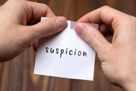Dealing with problem concept. Hands tearing paper sheet with inscription suspicion. Фото со стока