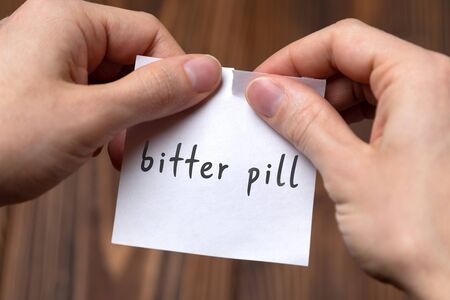 Dealing with problem concept. Hands tearing paper sheet with inscription bitter pill.