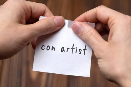 Dealing with problem concept. Hands tearing paper sheet with inscription con artist.