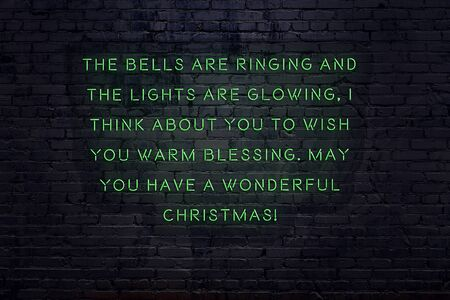 Neon inscription of christmas and new year greetings on brick wall.