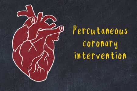 Learning cardio system concept. Chalk drawing of human heart on black chalkboard and inscription Percutaneous coronary intervention