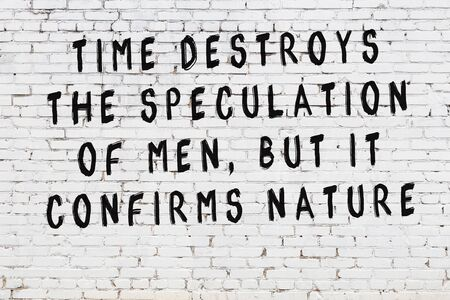 White brick wall with black painted inscription of sensible wise quote on it Stock Photo