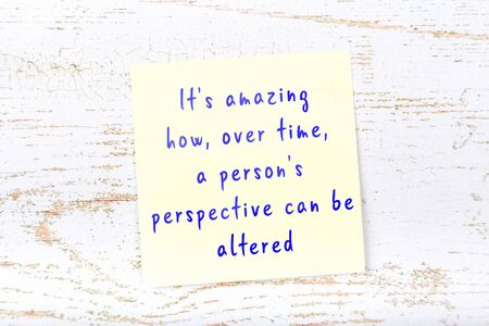 Wise quotation handwritten on yellow sticky note hanging on wooden wall