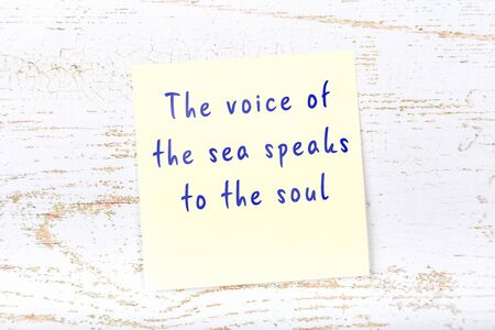 Wise quotation handwritten on yellow sticky note hanging on wooden wall Foto de archivo
