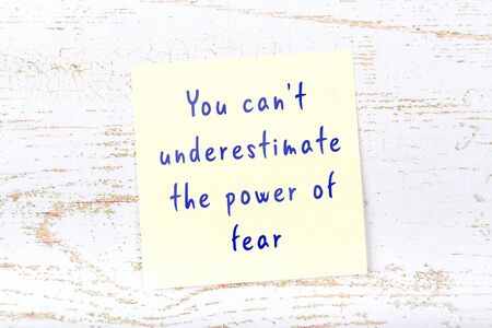 Yellow sticky note with handwritten motivational quotation on wooden wall