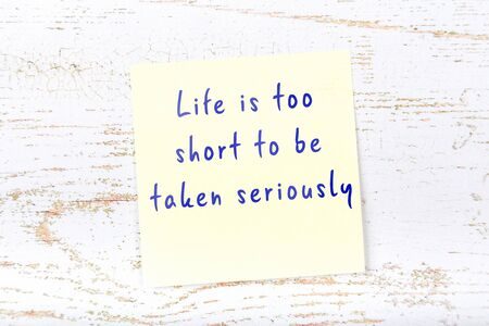 Yellow sticky note with smart quotation handwritten on it hanging on wooden wall Banco de Imagens