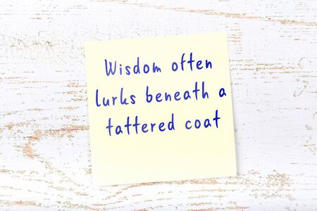 Yellow sticky note with smart quotation handwritten on it hanging on wooden wall 스톡 콘텐츠