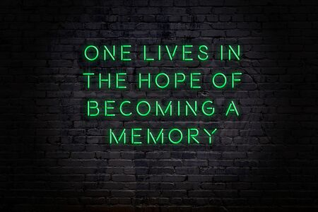Night view on neon inscription of wise quotation on brick wall