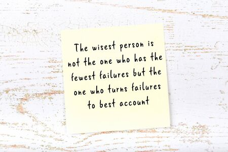 Yellow sticky note with smart quotation handwritten on it hanging on wooden wall
