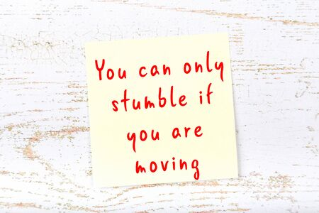 Yellow sticky note with handwritten motivational quotation on wooden wall Banque d'images