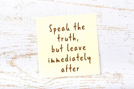 Yellow sticky note with handwritten motivational quotation on wooden wall 스톡 콘텐츠
