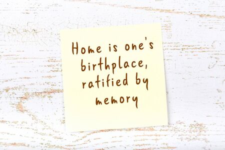 Yellow sticky note with smart quotation handwritten on it hanging on wooden wall 版權商用圖片