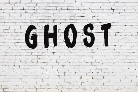 White brick wall with inscription ghost handwritten with black paint Banque d'images