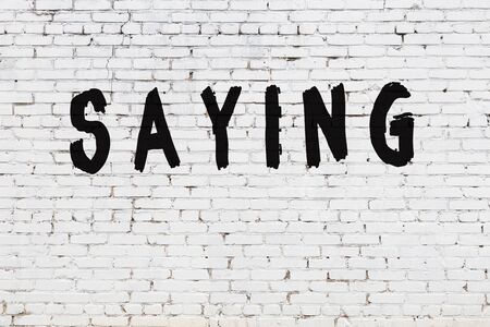 Word saying written with black paint on white brick wall. Banco de Imagens