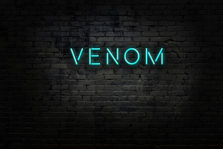 Neon sign with inscription venom against brick wall. Night view