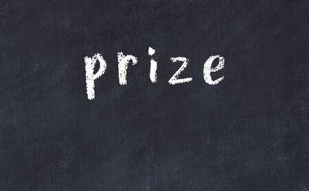 Chalk handwritten inscription prize on black desk