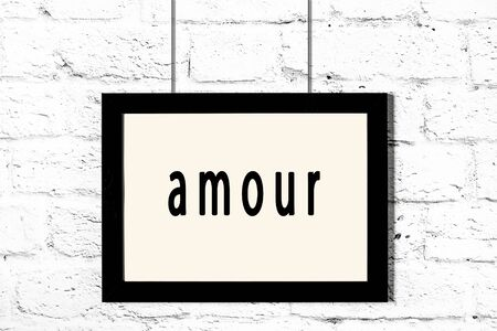 Black wooden frame with inscription amour hanging on white brick wall