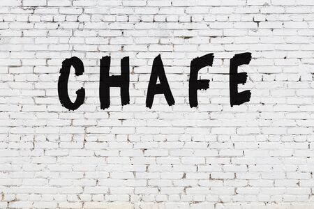 Word chafe written with black paint on white brick wall.