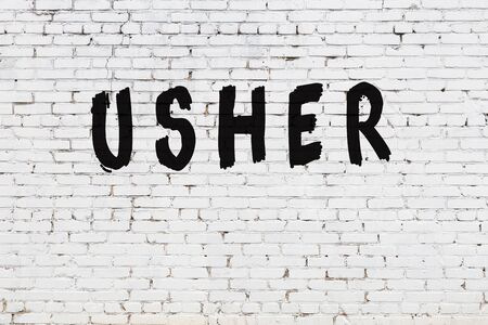 Word usher written with black paint on white brick wall.