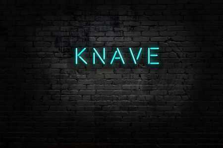 Neon sign with inscription knave against brick wall. Night view