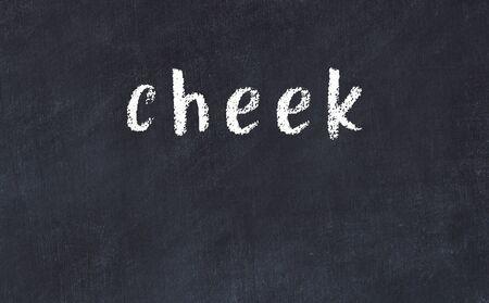 Chalk handwritten inscription cheek on black desk Stock Photo