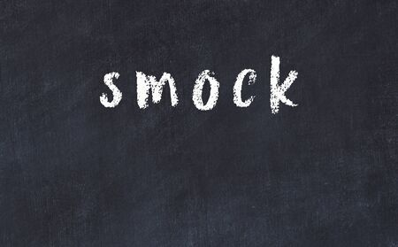Chalk handwritten inscription smock on black desk