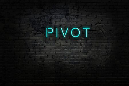 Neon sign with inscription pivot against brick wall. Night view
