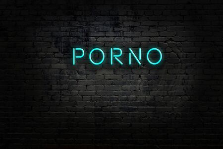 Neon sign with inscription porno against brick wall. Night view