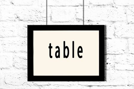 Black wooden frame with inscription table hanging on white brick wall