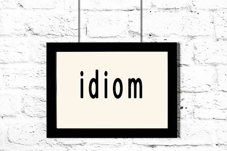 Black wooden frame with inscription idiom hanging on white brick wall