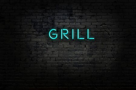 Night view of neon sign on brick wall with inscription grill