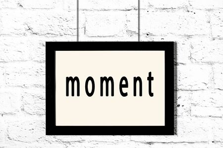 Black wooden frame with inscription moment hanging on white brick wall Imagens