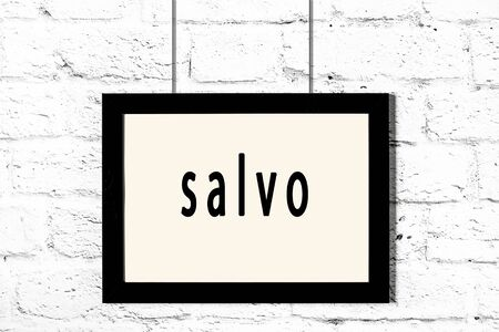 Black wooden frame with inscription salvo hanging on white brick wall Stok Fotoğraf