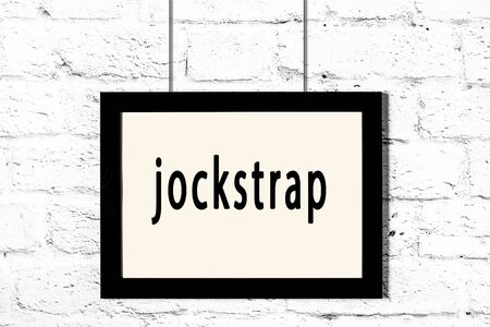 Black wooden frame with inscription jockstrap hanging on white brick wall