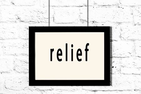 Black wooden frame with inscription relief hanging on white brick wall Standard-Bild