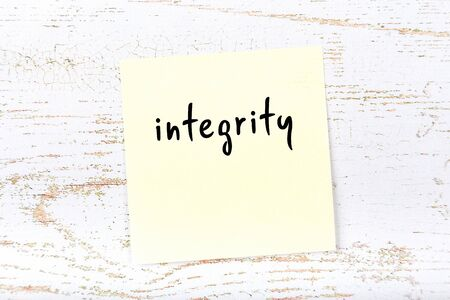 Concept of reminder about integrity. Yellow sticky sheet of paper on wooden wall with inscription 스톡 콘텐츠